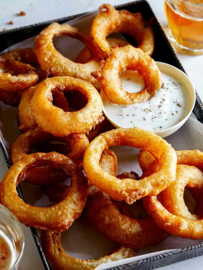 A serving of beer battered fried onion rings with ranch.