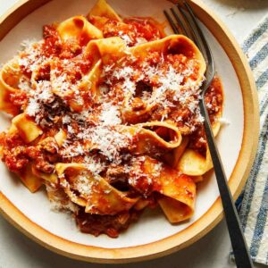 Bolognese sauce with parmesan and pasta in a bowl.