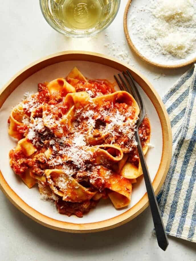 Bolognese sauce with pasta in a bowl and parmesan on the side.
