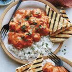 Butter chicken on a plate with rice.