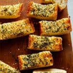 Garlic bread on a cutting board cut up.