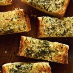 Close up on homemade garlic bread cut into slices on a cutting board.