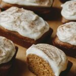 Pumpkin Bars with one cut in half on parchment.