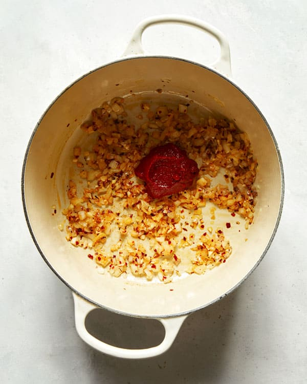 Onions and tomato paste in a stock pot.