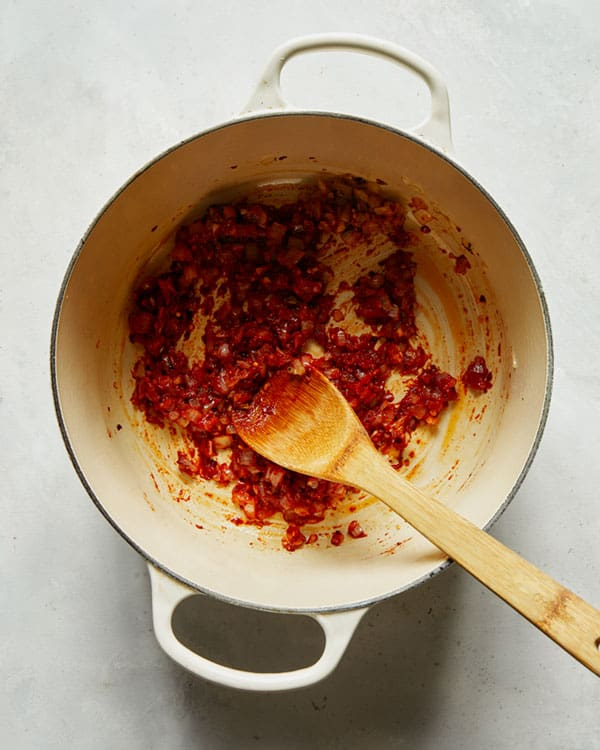 Tomato paste and onions in a stock pot to make arrabiata sauce.