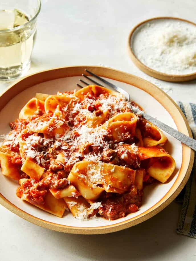 Bolognese sauce with pasta in a bowl with wine in the background.