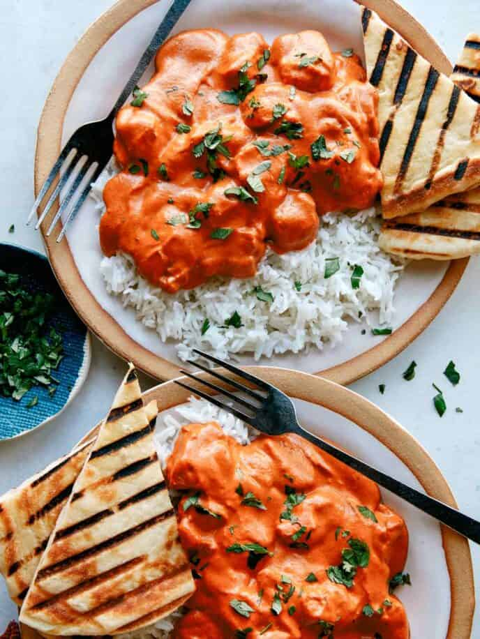 Two servings of butter chicken on plates with bread and rice.