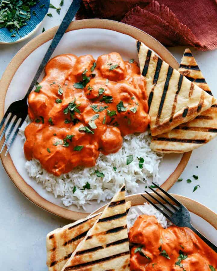Butter chicken, or murgh makhani recipe on two plates with rice.