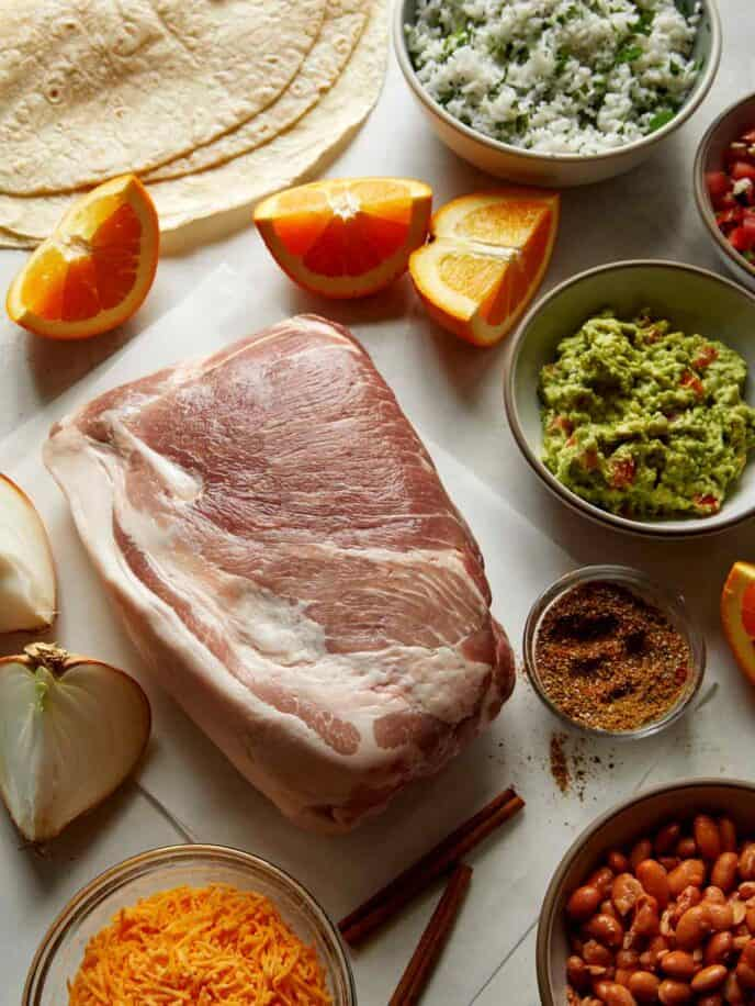 Pork carnitas ingredients all laid out on a kitchen counter.