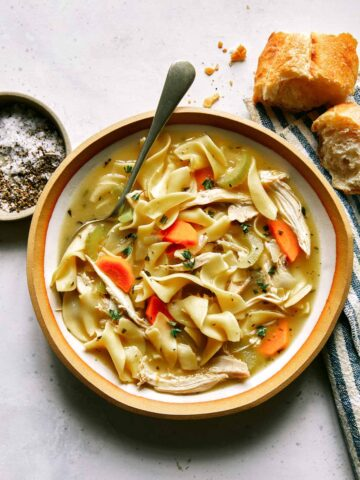 Chicken noodle soup recipe in a bowl with bread on the side.