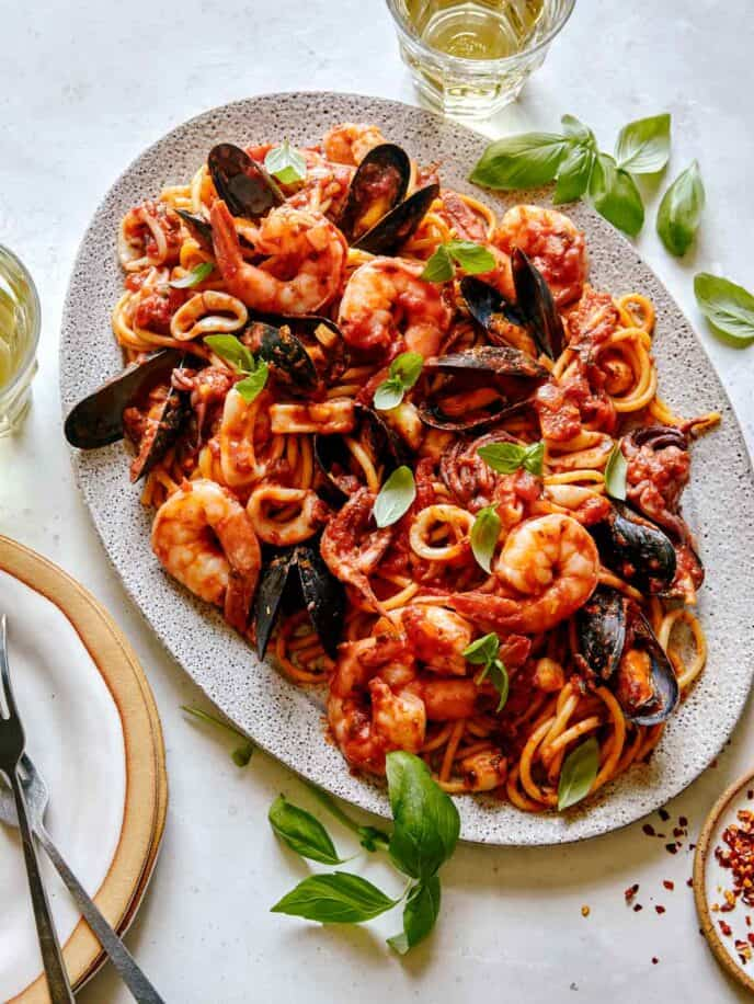 Frutti Di Mare recipe on a platter with basil leaves on the side.