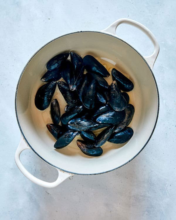 Mussels cooking in a pot with garlic and oil to make Frutti Di Mare.