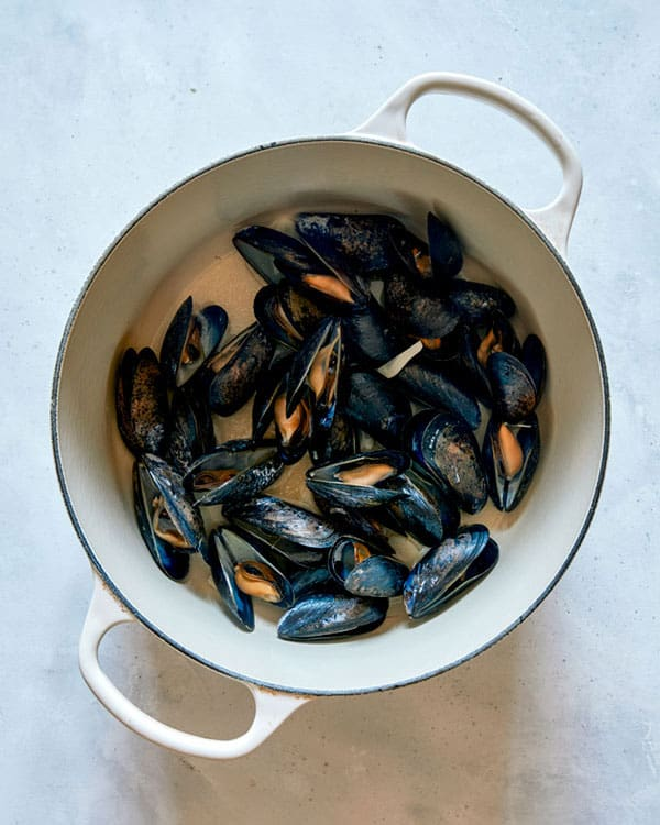 Cooked mussels in a pot with oil and garlic.
