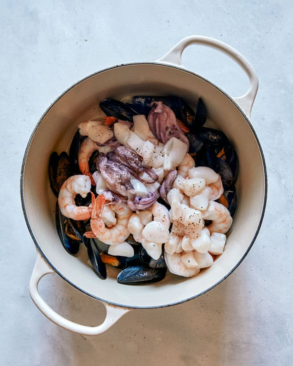 Seafood being cooked in a pot to make frutti di mare.