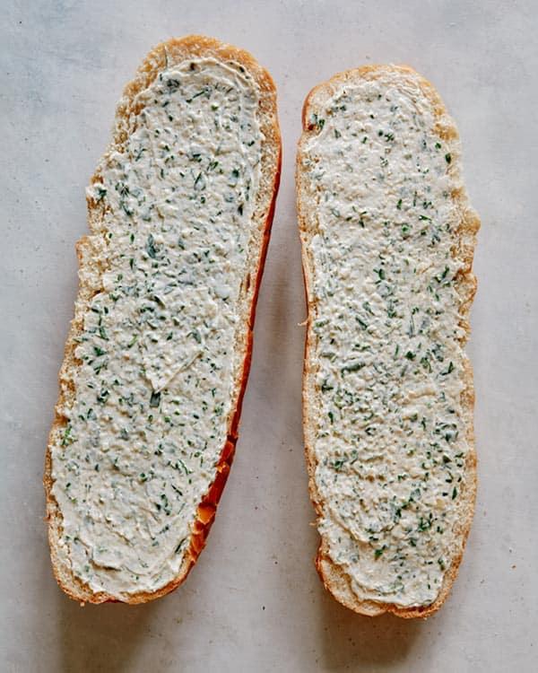 Garlic bread butter spread onto bread ready to go into the oven.