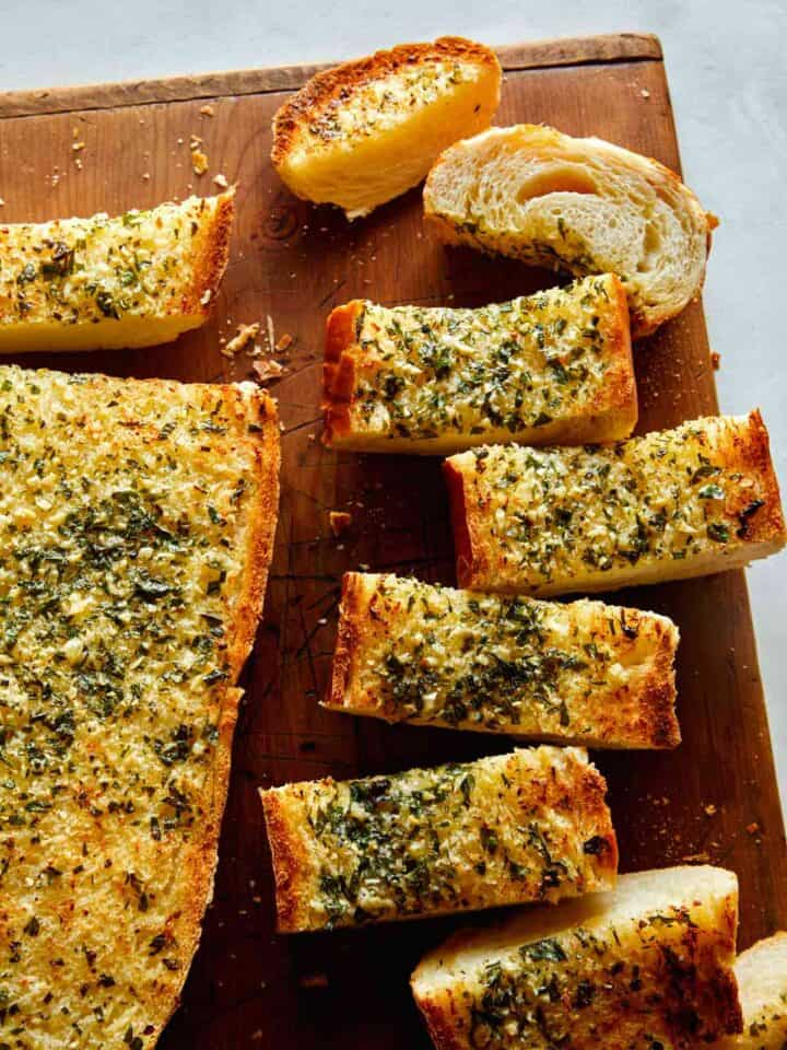 Homemade garlic bread recipe on a cutting board with some cut up.