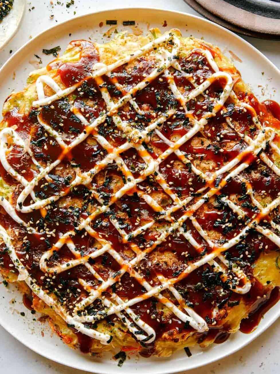 Okonomiyaki on a plate with fork next to it.