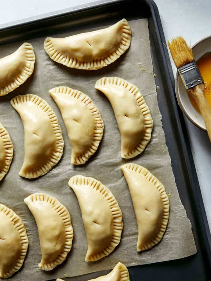 Pork pasties on a baking sheet being brushed with an egg wash.