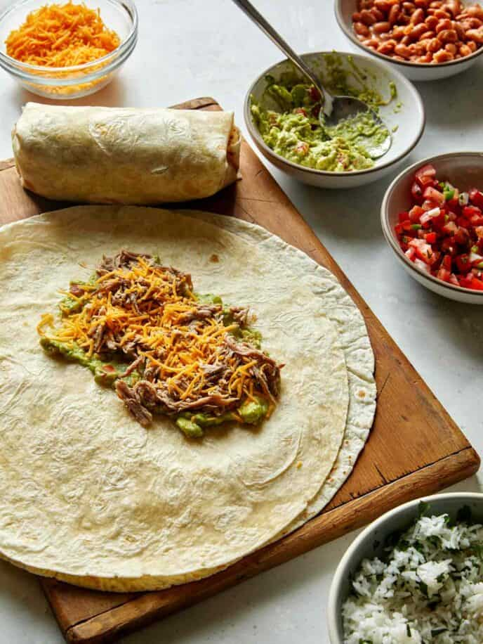The process of making a pork burrito with a tortilla.
