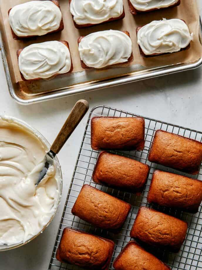 Pumpkin bars being topped with cream cheese frosting.