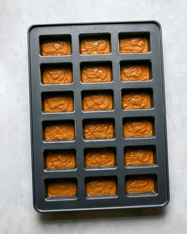 Pumpkin bar batter poured into a prepared baking sheet.