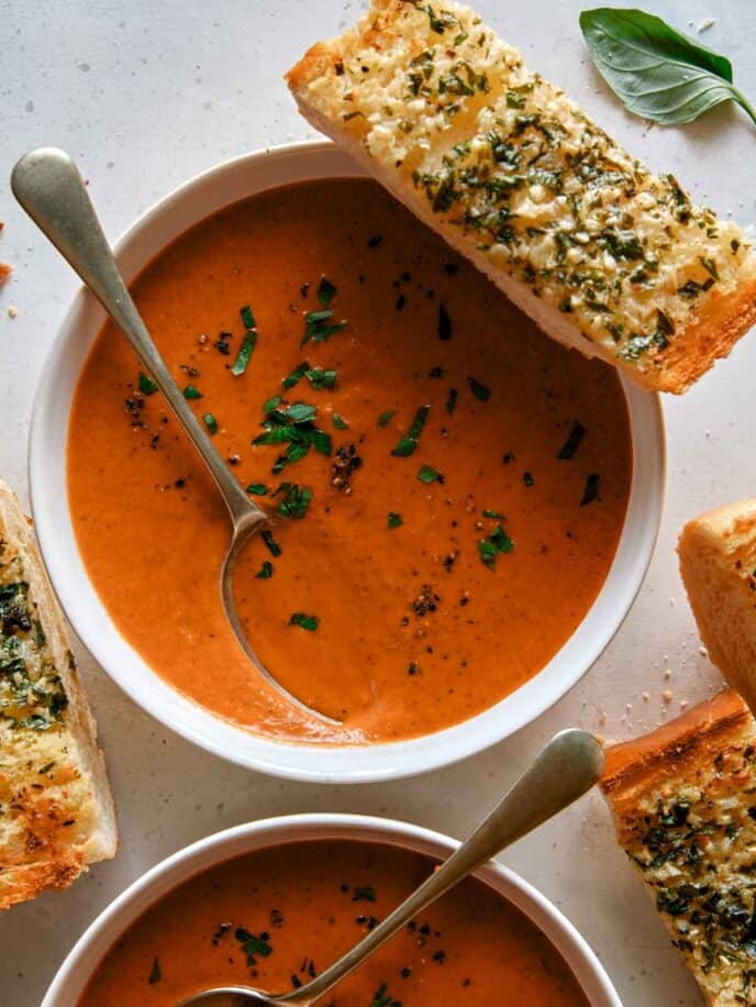 Tomato soup recipe in two bowls with garlic bread.