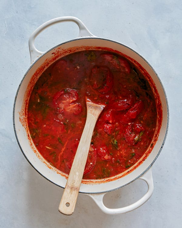 Tomato soup simmering in a stock pot.