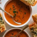 Tomato soup recipe in two bowls with garlic bread on the side.