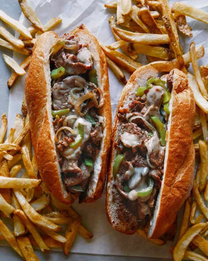 Two Philly Cheesesteak sandwiches with french fries.