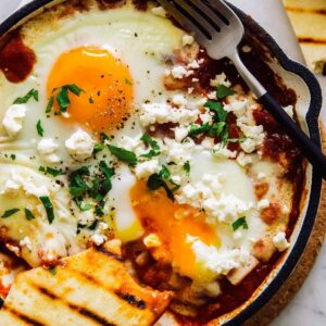 Individual shakshuka with hominy and feta, with a popped egg yolk and grilled flatbread.