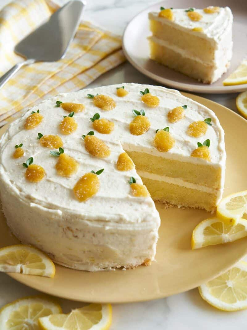 A lemon thyme layer cake with a piece cut out on a plate and lemon slices.