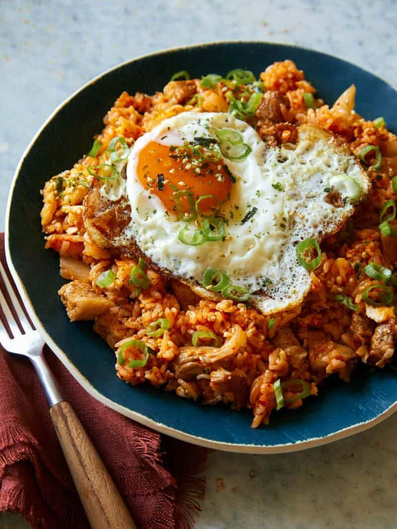 A close up of kimchee fried rice in a bowl with a fork.